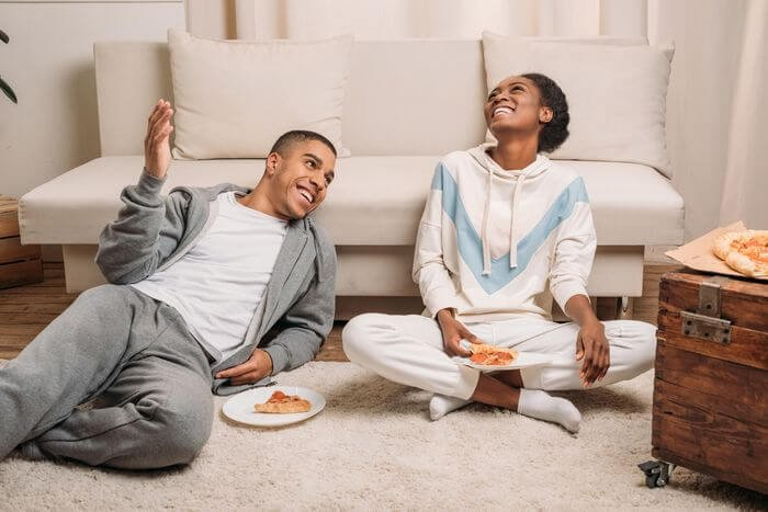 African couple eating pizza